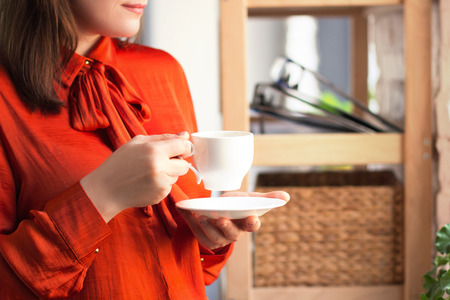 Lady turnt to side with little white cup in her hands. Young businesswoman dressed in bright bold coloured shirt with bow in front having coffee break.