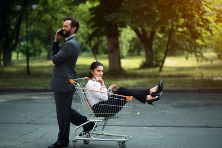 business woman sitting in cart. Man standing behind. showing his superiority.