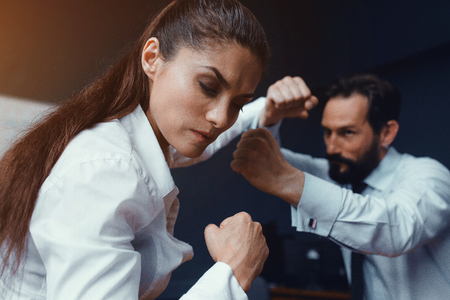 Man and woman imitate boxing while being in office. Compete in business. Fight of genders concept. 版權商用圖片