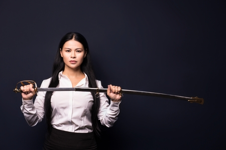 Beautiful business woman posing on camera with sword. Showing power. Business concept.