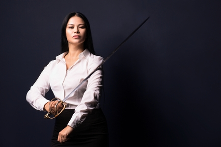 Half length image of brunette business woman with sword in hands. Isolated on dark background.