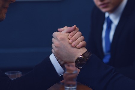 Men in suit or businessmen with tense faces compete in armwrestling on table on dark background. Imagens