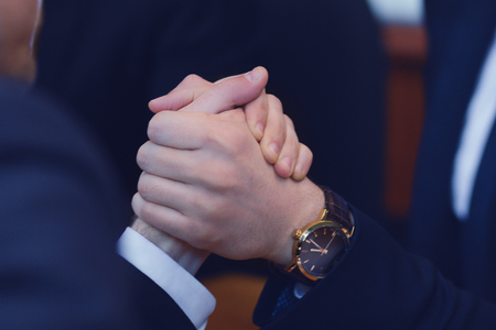Male hands compete in armwrestling after signing agreement. Business power concept.