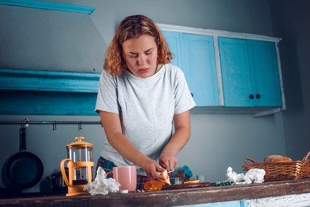 Shot from slightly below on the woman in blue t-shirt slicing lemon to make a tea. Blonde girl feeling unwell is cutting lemon. Used tissues and pills all around on the wooden table 版權商用圖片 - 111757399