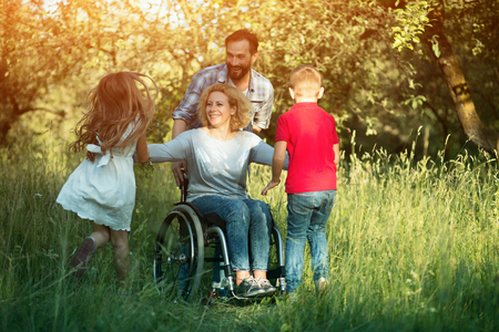 Smiling Woman In Wheelchair And Man Standing Behind Her Smiles At Children Who Run To Them. Disabled Mother Plays With Her Kids In The Park.