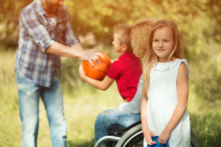 Beautiful Blonde Girl On Foreground Is Looking At Camera And Smiles. Blurred Image Of Man Throwing Ball To Little Boy, Who Sits On The Knees Of His Disabled Mother In A Wheelchair On The Background Banque d'images