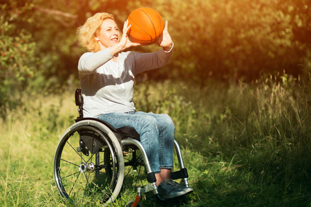 Smiling Paraplegic Girl In Wheelchair Throws A Basket Ball. Beautiful Girl In Wheelchair Is Playing Basketball Outside.