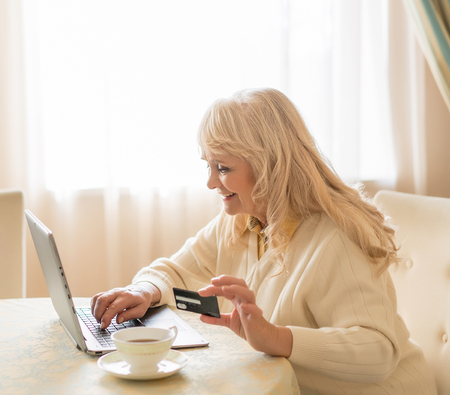 Shopping Online. Elegant Mature Woman Types On The Laptop While Holding The Credit Card. Cup Of Tea Stands Near The Laptop On Which Woman With A Banking Card Prints On.