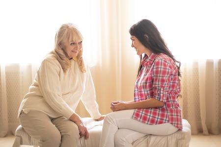 Mère aînée regarde étonnamment sa charmante fille lui parler de quelque chose. Du temps en famille. Unité