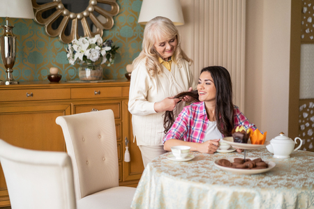 Caring Senior Mother Delicately Touches The Long Hair Of Her Brunette Daughter. Smiling Woman Sits At The Table And Drinks Tea While Her Elderly Mother Tackles Her Hair. Stock Photo