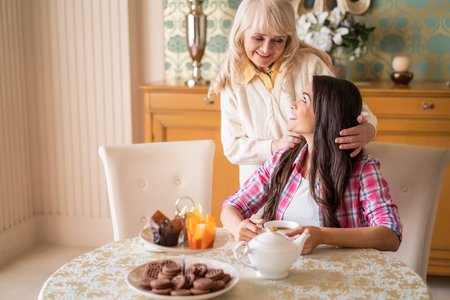 Lovely Mother Cuddles The Hair Of Beautiful Daughter. Happy Brunette Girl Sits At The Breakfast Table While Her Senior Mother Tucks Her Hair