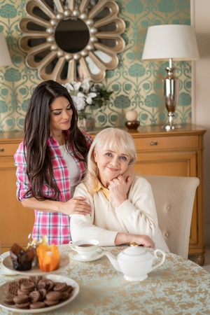 Charming Young Daughter Hugs Tight Her Elderly Mother, Who Sits At The Table In Living Room. Family Relationship. Tea With Mother. Banque d'images - 113646042