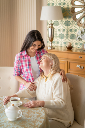 Elderly Woman Drinks Black Tea And Looks At Her Lovely Daughter Who Hugs Her Tightly Banque d'images - 113646130