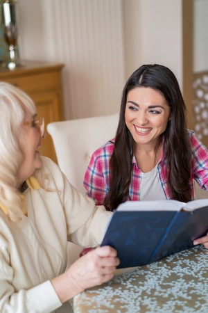 Vertical Shot Of Cheerful Girl Smiling To Her Elderly Mother Who Reads A Hard-Covered Book In The Living Room At The Table. Banque d'images - 113646174