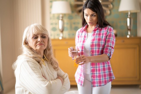 Worried Daughter Tries To Persuade Her Mother To Take Medication. Senior Woman Refuses To Take Pills.