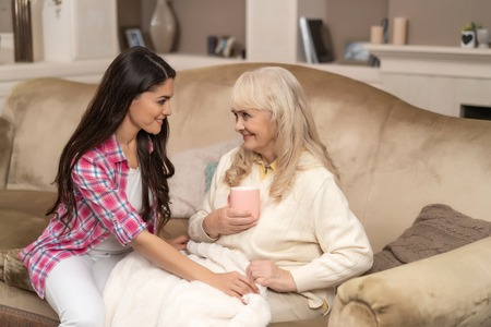 Senior Woman Holds A Cup Of Aromatic Tea While Her Charming Daughter Covers Her With Warm Blanket 写真素材
