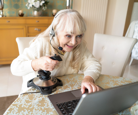 Portrait Of Elderly Mother In Headphone Sitting At The Screen Of Laptop And Playing A Video Game With A Help Of Joystick. Gamer.