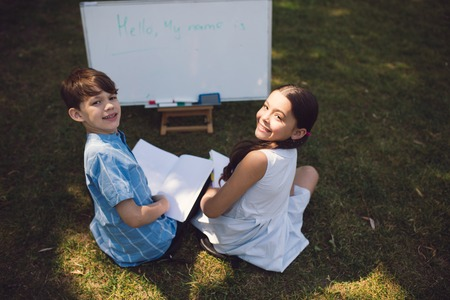 School Children Sitting On Grass And Having Maths Lesson. Writing On Whiteboard. Education In Nature Concept.
