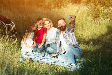 Handsome Father Takes Selfie Of Him And His Family Laying On The Blanket In The Park. Wheelchair.