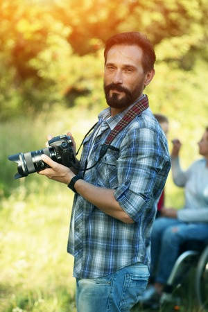 Portrait Of Handsome Man With Beard Holding Professional Camera And Thinking Over Next Shot. Blurred Image Of Woman In Wheelchair On The Background Banque d'images