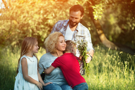 Caring Husband Presents Wild Flowers To Woman In Wheelchair While She Hugs Son And Daughter. Outdoor