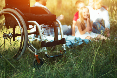 Detailed Shot Of Wheelchair Standing Empty On The Foreground While Happy Family Is Resting On The Picnic Behind It. Special Equipment For Disabled People.