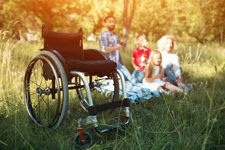Close-Up View On The Modern Special Wheelchair Which Stands Empty On The Grass. Blurred Family Is Having Fun In The Background 免版税图像