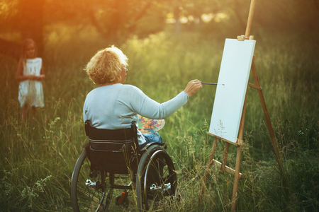 Peaceful Time In The Park Where Woman In Wheelchair Paints On The Wooden Easel While Her Little Daughter Admires Her Picture.
