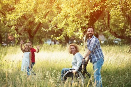 Beautiful Woman In Wheelchair With Her Husband Holding The Push Handles Look Back And Smiles At Somebody. Two Charming Kids Are Waving.