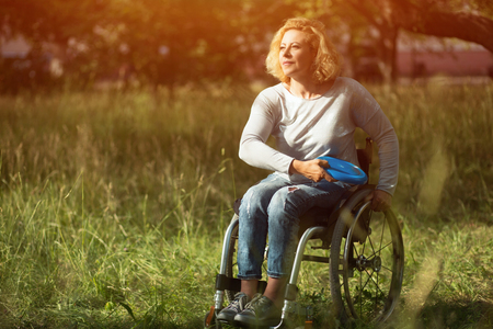 Beautiful Blonde Woman Is Sitting In Wheelchair And Having Fun By Playing And Throwing flying disk. Recovery From Injury.