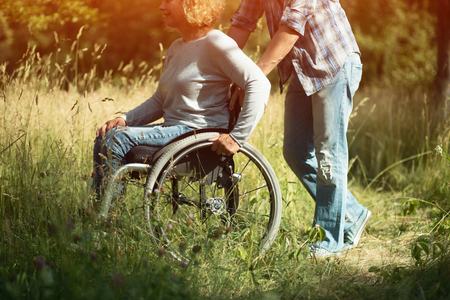 Bright Shot Of Man Taking Care Of His Disables Wife And Moving The Wheelchair. Half-Size Picture Of Woman On A Wheelchair And A Man Pushing It Фото со стока