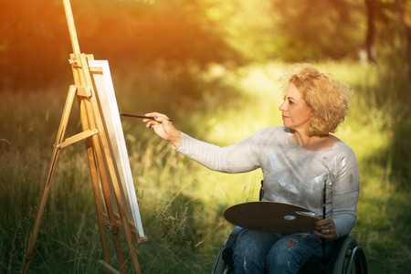 Horizontal Shot Of Inspired Woman In Wheelchair Painting On The Big Easel Outdoor. Recovery Concept.