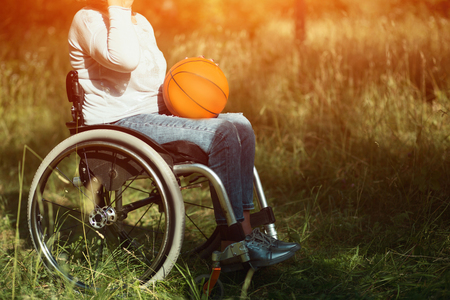 Bright Shot Of Woman Sitting In A Wheelchair With A Basket Ball On Her Knees. Outdoor. Recovery Stock Photo