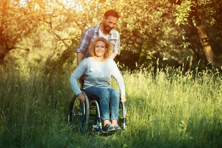 Disabled Woman In An Armchair Enjoys Her Time With A Handsome Partner In The Sunny Warm Park.