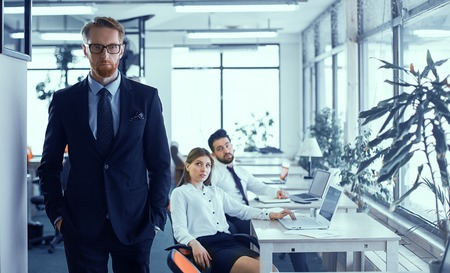 Bearded red-haired boss is standing in a stack of dark suit, pondered working plans. Colleagues are scornfully watching their supervisor