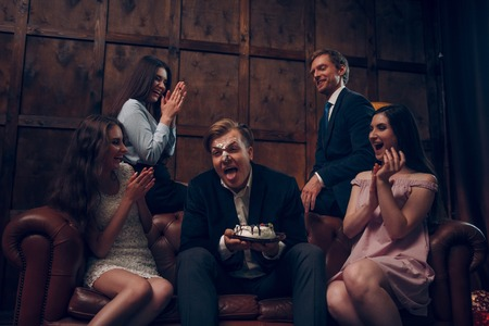 Laughing hard at young man whose face is covered with piece of birthday cake. Man whose face is in cake sticks his tongue to lick his lips Stock Photo
