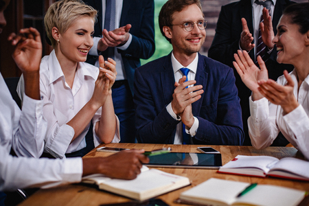 Happy Group Of Business People Clap Hands After Meeting. Charming Colleagues Celebrate Their Deal By Applauds. Foto de archivo