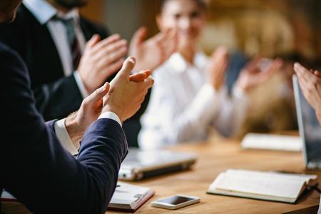 Aplaudiendo un gran éxito. Enfoque selectivo en manos de hombres de negocios aplaudiendo en una reunión. Concepto de éxito empresarial.