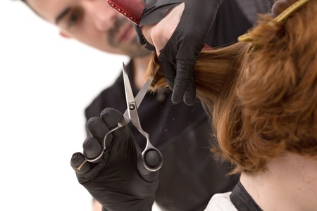 Selective Focus On Barbers Hands Holding Scissors And S A Comb And Trimming Hair. Closeup Of Trimming Clients Hair.