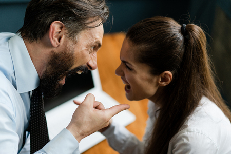 Arguing Colleagues. Bearded Man In A White Short And A Tie Bend Over The Female College Pointing Finger. Serious Woman Looks At Her Boss And Points Her Finger. Disagreements At A Working Place. Top View