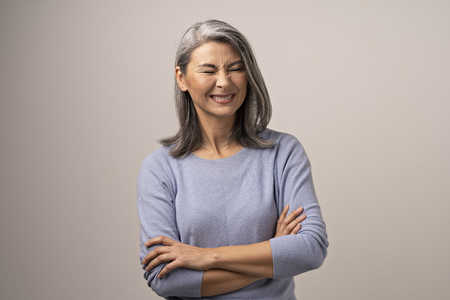 Graceful Mature Woman With Crossed Arms Wrinkles Her Nose. Middle-Aged Asian Woman With Crossed Arms Wrinkling Her Nose And Smiling. Portrait.
