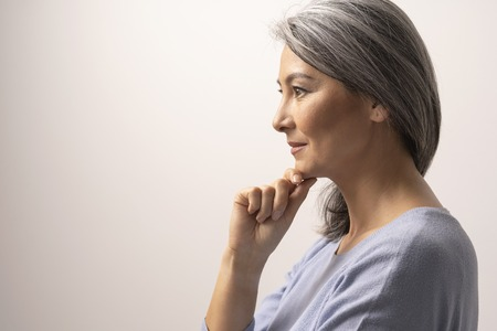 Smiling Asian Woman With Grey Hair Touches The Chin. Beautiful Middle-Aged Woman In Profile Touching Chin.