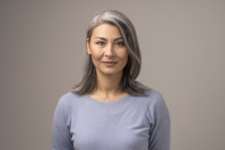 Beautiful Mongolian Woman with Gray Hair on a Gray Background. Womans Face Has a Relaxed Smile. She is Wearing a Soft Blue Blouse. Close Up Shoot.