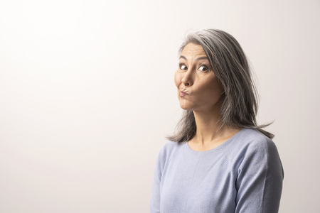 Mongolian Woman with gray hair on a White Background.. She has a thoughtful look. A womans face looks funny. Close Up Shoot. Standard-Bild