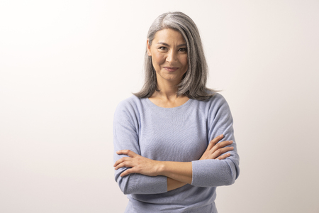 Beautiful Senior Asian Woman Crosses Her Arms And Smiles. Smiling Grey-Hair Woman With Crossed Arms. White Background. Portrait.