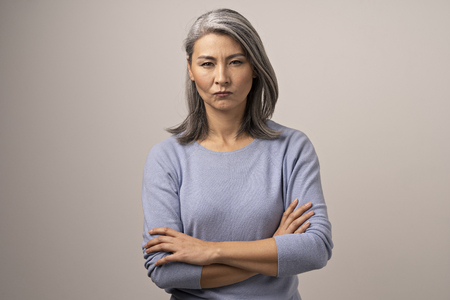 Serious Mongolian Woman with Gray Hair Against the Backdrop of Gray. The Woman Has An Evil Look. Arms Crossed She Shows Her Displeasure. Close Up Shoot. Stock Photo