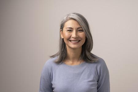 Charmante Asiatin mittleren Alters lächelt breit in die Kamera. Horizontale Studioaufnahme der würdevollen lächelnden Frau. Porträt Standard-Bild