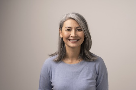 Charming Middle-Aged Asian Woman Broadly Smiles At Camera. Horizontal Studio Shot Of Graceful Smiling Woman. Portrait 写真素材 - 118959837