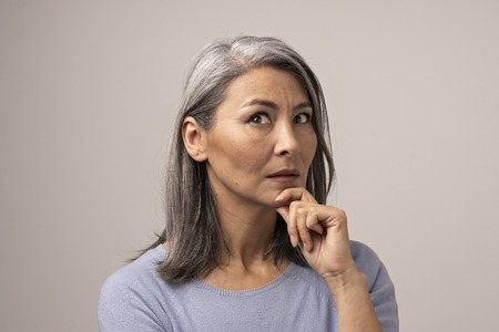 Mongolian-Looking Woman with Gray Hair on a Gray Background. Her Face Looks Thoughtful. The Woman s Gaze is Directed Upwards. Her Hand Props Her Chin. Close Up Shoot. Banco de Imagens