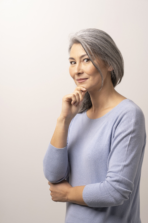 Charming Woman Touching Her Chin With One Hand. Happy Asian With Grey Hair Lightly Smiles And Delicately Touches Her Chin With Hand. Studio Photoshoot.